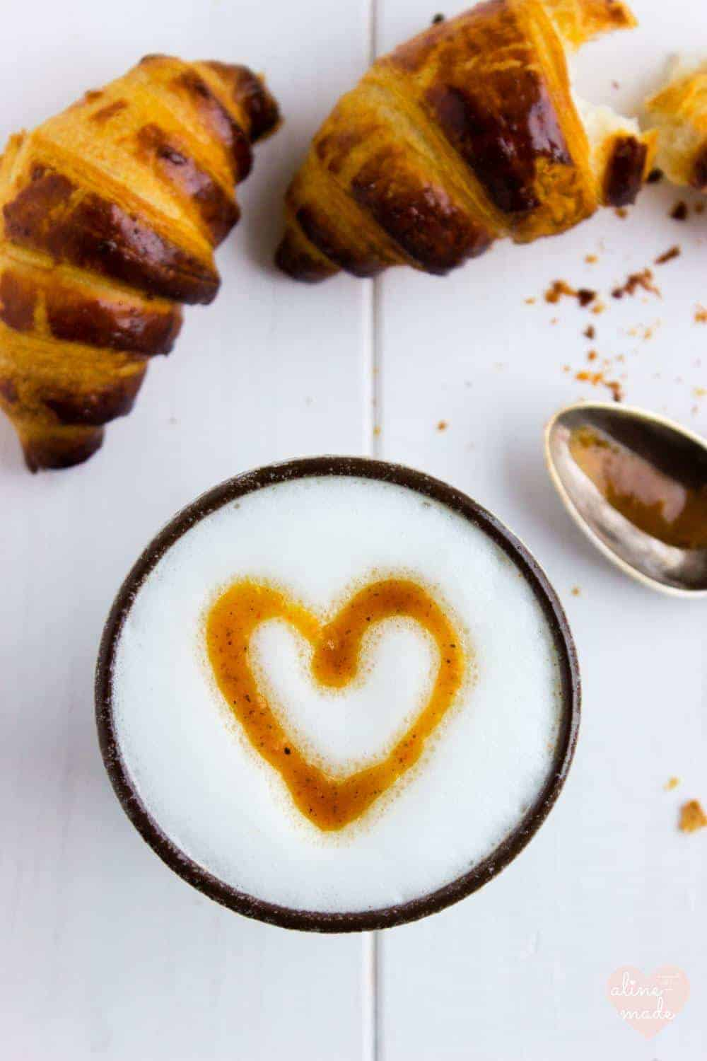 Pumpkin Spice Latte with a heart shape on the milk foam and croissants