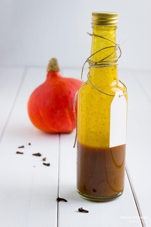 Pumpkin Spice Syrup in a glass bottle next to a pumpkin