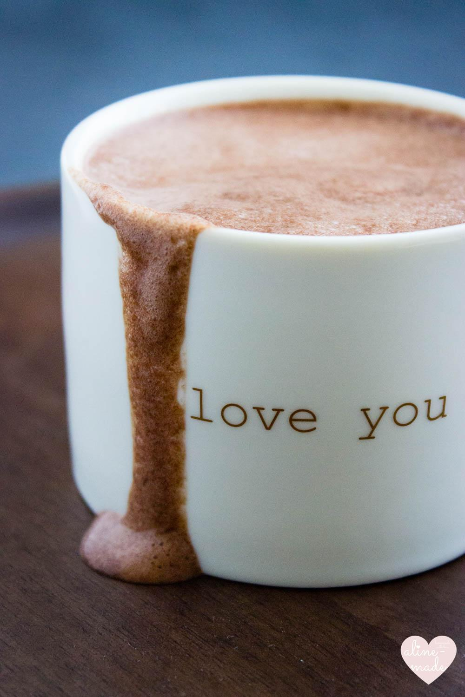 Vegan Hot Chocolate with a chocolate milk foam running down the mug