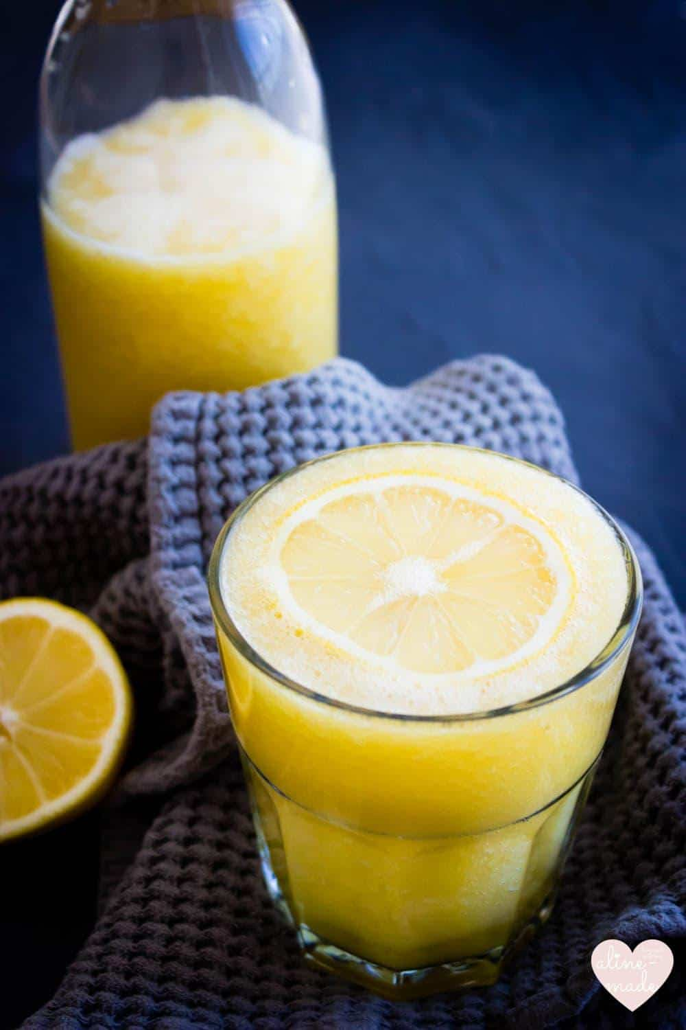 Simply Mango Lemonade in bright yellow topped with a lemon slice in