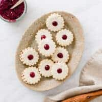 vegan linzer cookies served on a brown plate
