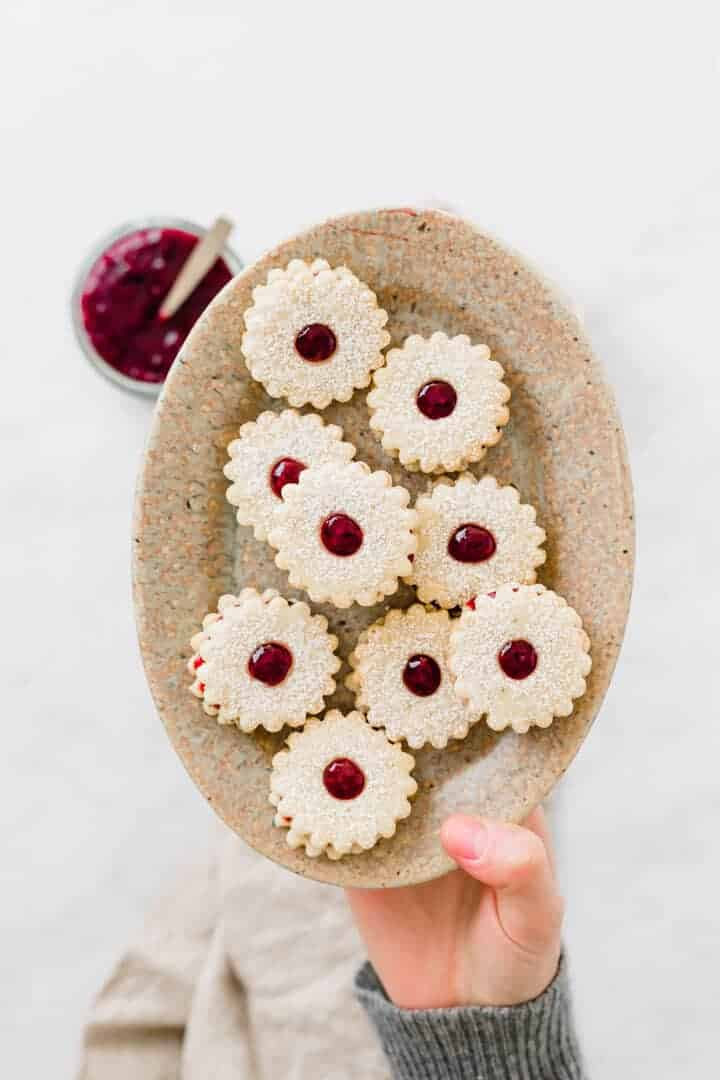 christmas linzer cookies served on a brown plate