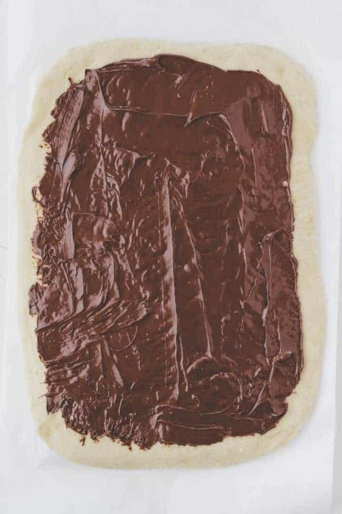 rechteckig ausgewallter zopfteig mit nutella bestrichen