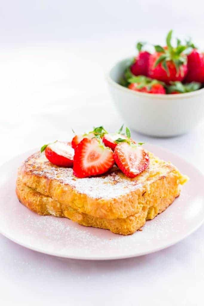slice of brioche french toast with fresh strawberries on top