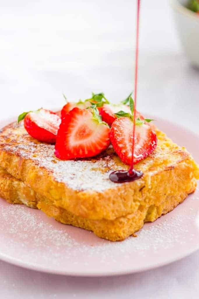 sweet french toast topped with strawberries and honey on a pink plate