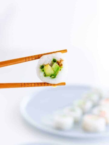 Homemade sushi hold between two chopsticks