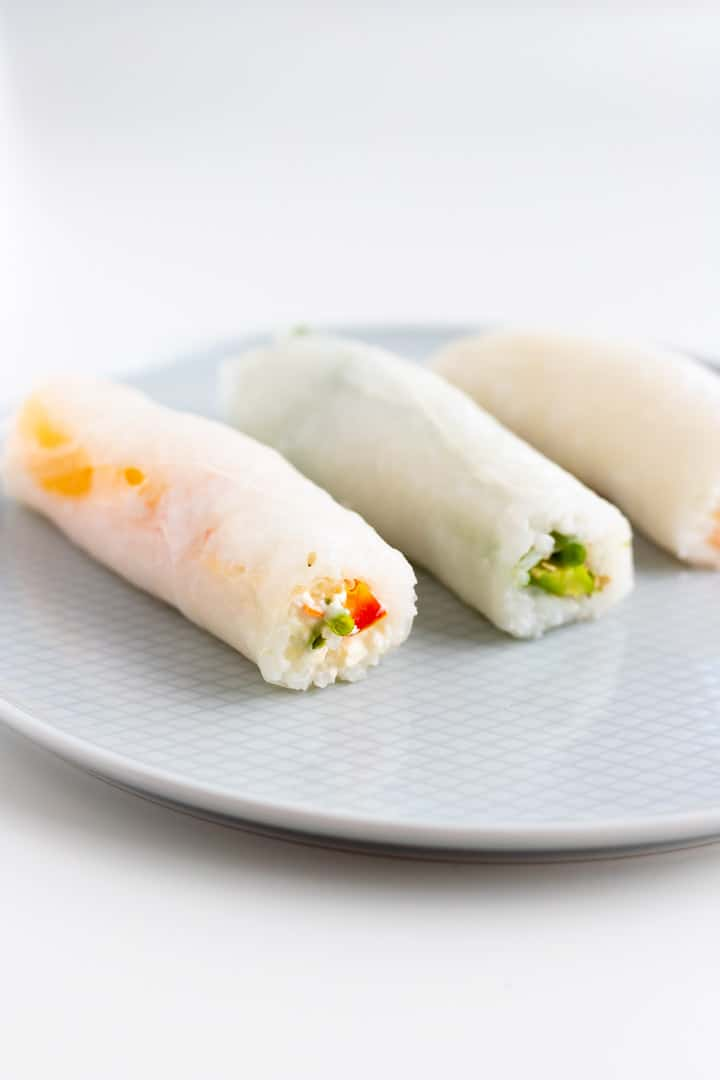 three homemade sushi rolls with vegetables and rice paper