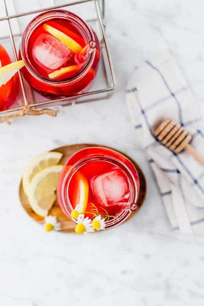 roter eistee serviert in einem glas mit eiswüfeln und zitrone