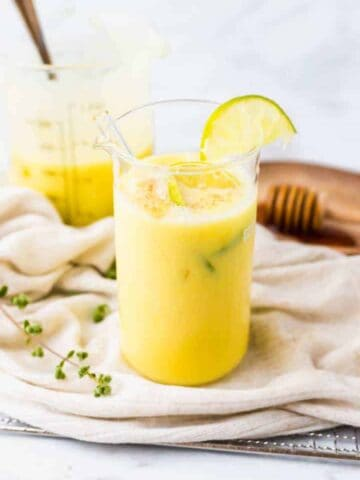 vegan mango lassi served in a large glass with lime slices
