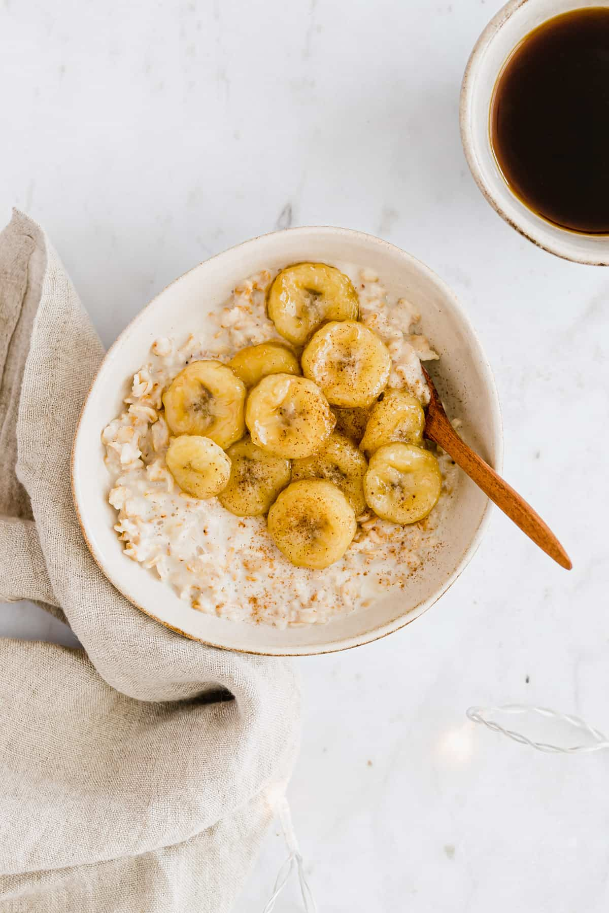 banana oatmeal next to a cup of coffee