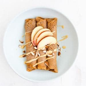 gluten-free buckwheat crepes topped with almonds, almond butter, and nectarine wedges