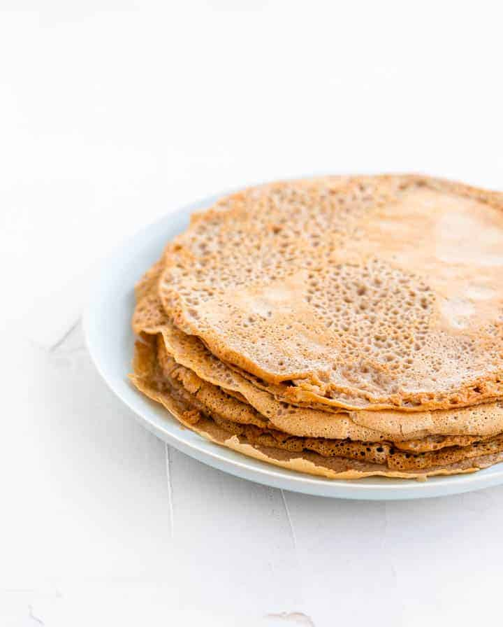 cooked buckwheat crepes on a blue plate