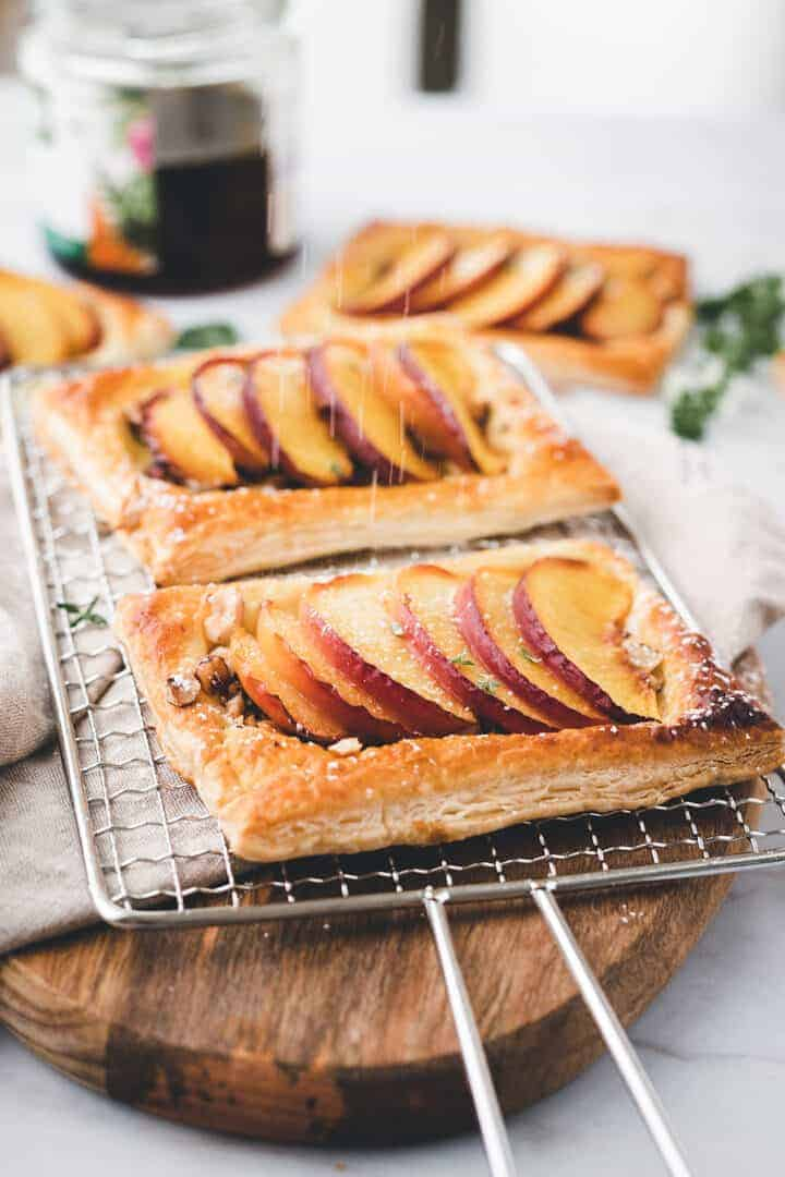 caster sugar sprinkled peach tarts on a wooden board