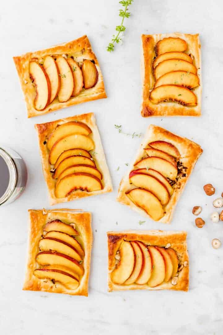 peach puff pastry tarts on a marble dish