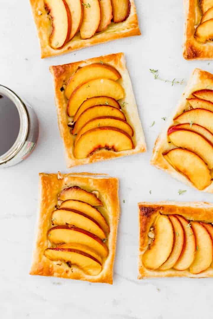 nectarine tarts next to a glass of maple syrup