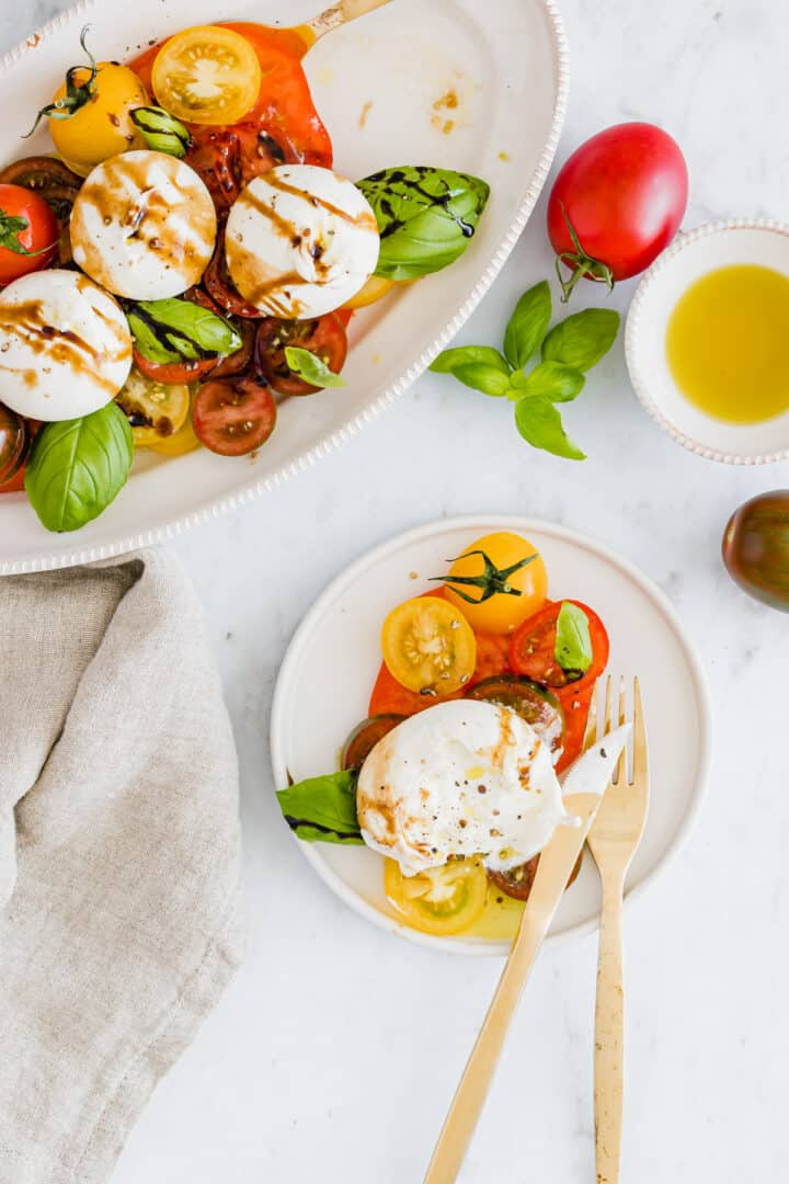 burrata salad with tomatoes served on plates