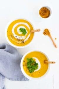 vegan potato soup served with vegan cream, curry powder, and greens