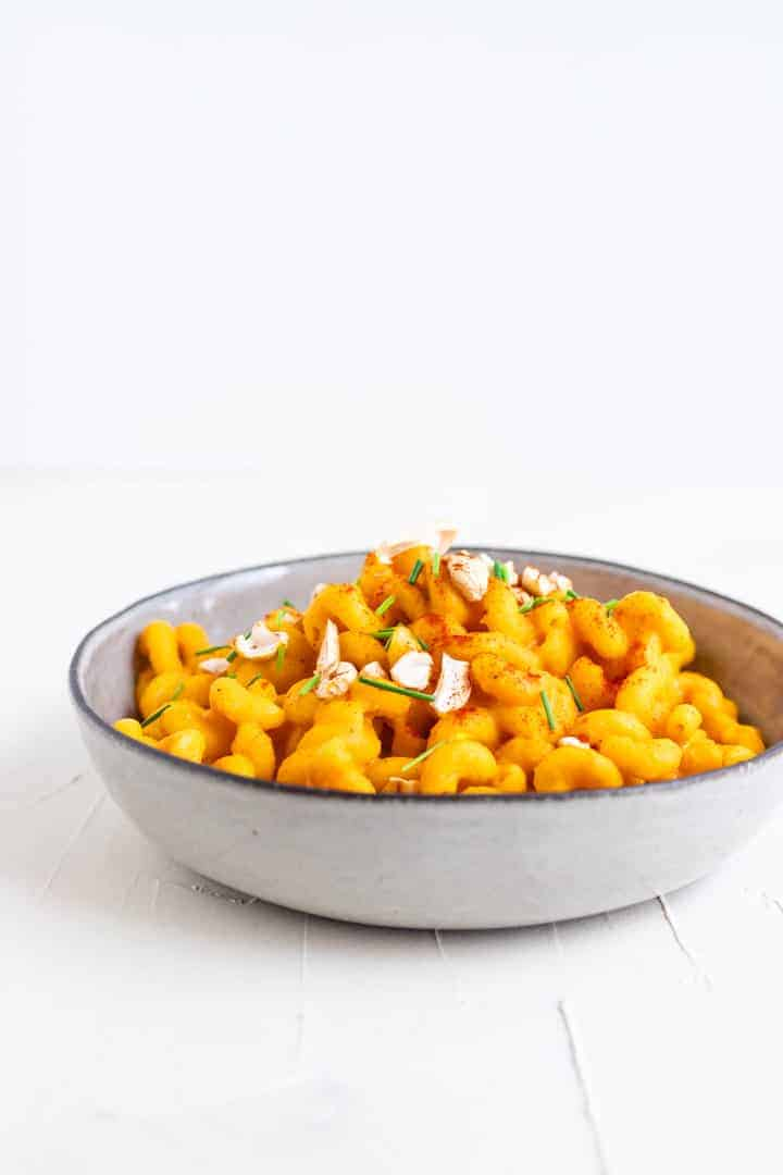 vegan pumpkin pasta served in a grey plate on a white table