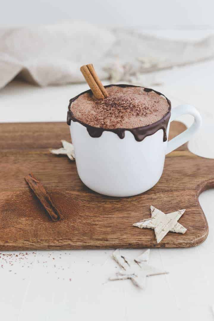 vegan hot chocolate with cinnamon on a wooden board
