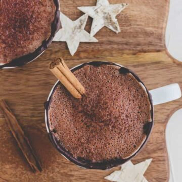 best vegan hot chocolate recipe on a wooden board with little starts and a cinnamon stick