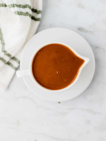 vegan gravy served in in a white saucier next to a towel