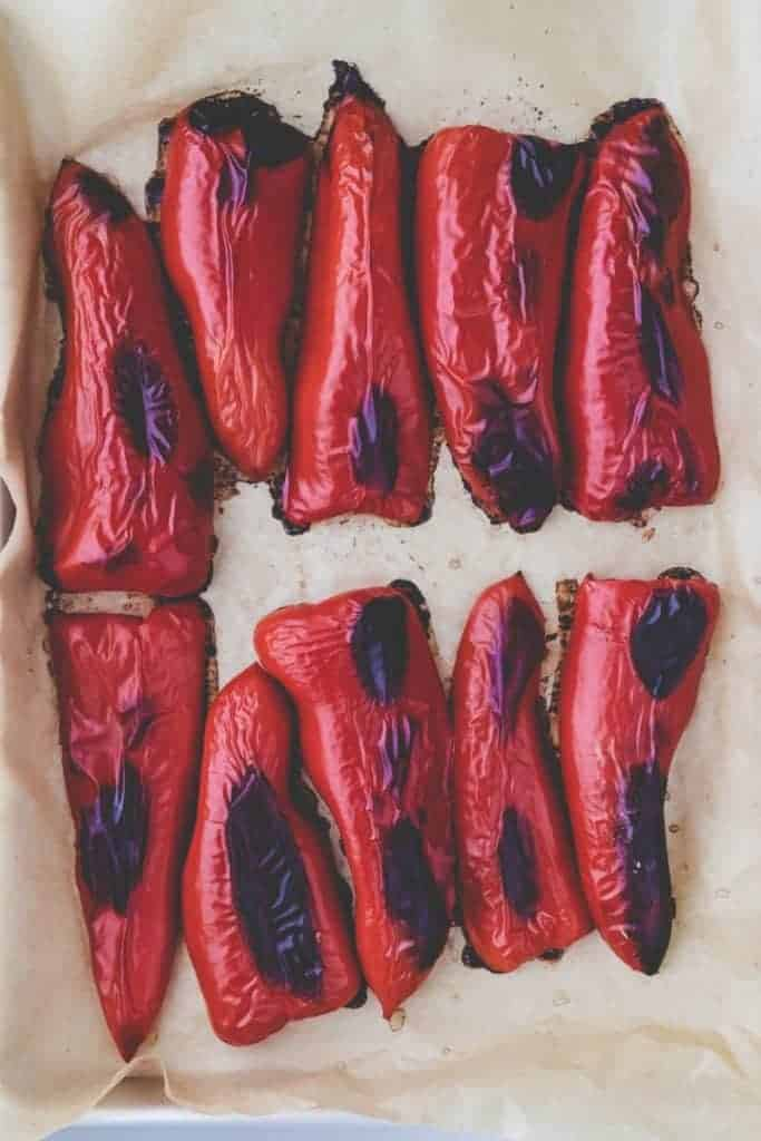roasted red peppers on a parchment paper after they are coming out of the oven