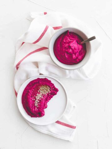 beetroot hummus in two white cups on a white towel