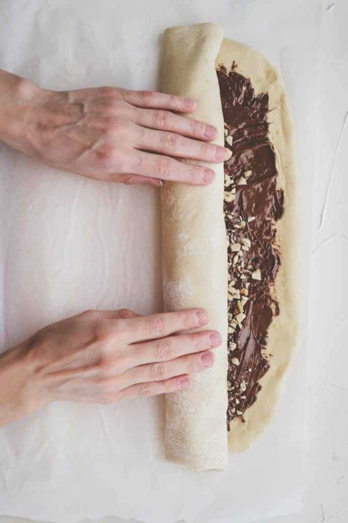 rolling up babka dough spread with nutella and topped with hazelnuts using hands