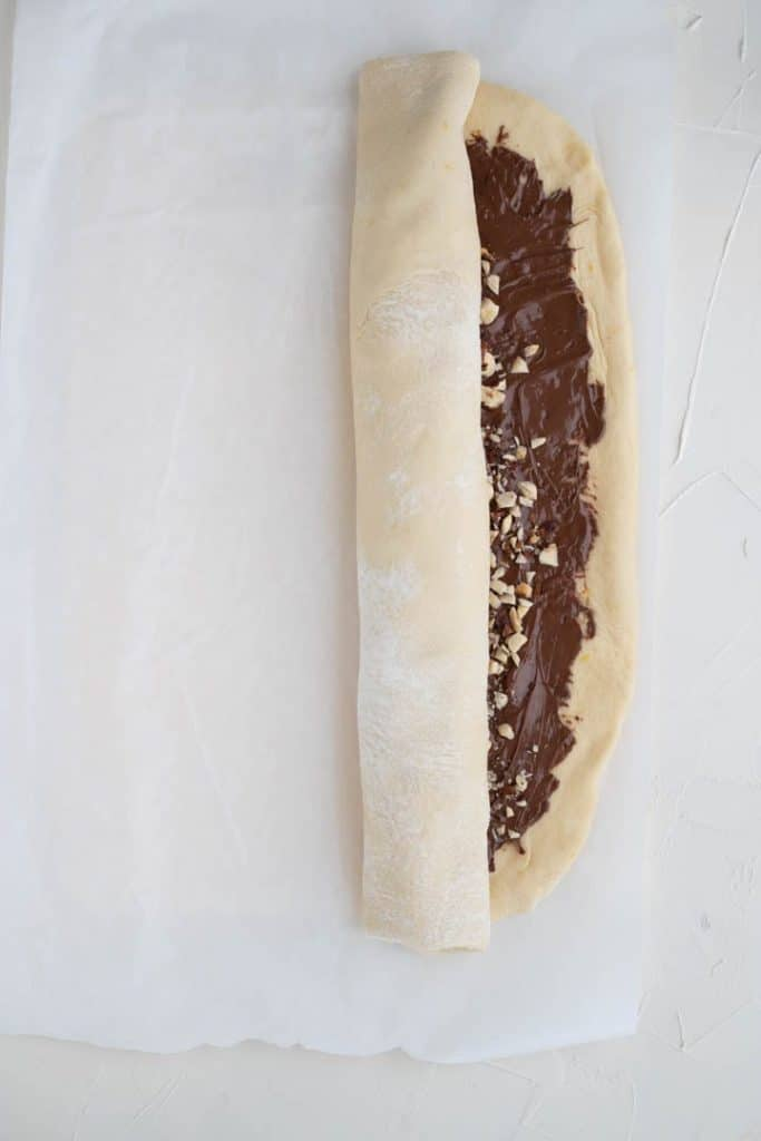 rolled up babka dough spread with nutella and topped with hazelnuts