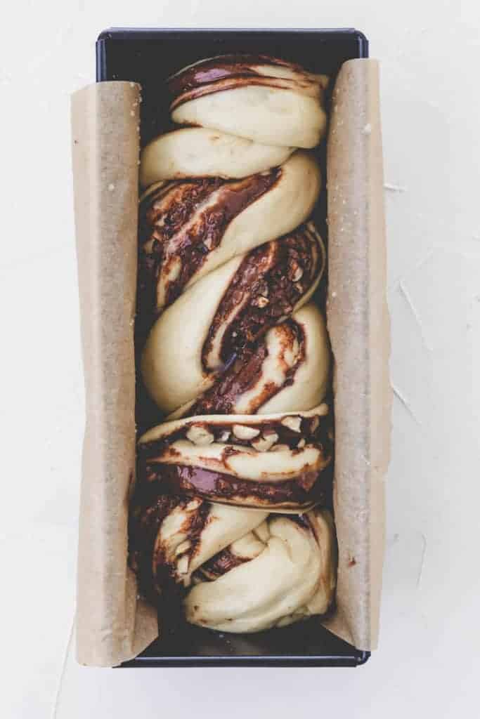 braided nutella bread in a with parchment paper lined loaf pan