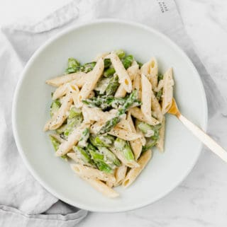 creamy asparagus pasta on a blue plate