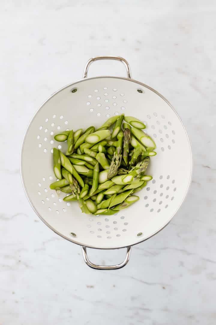geschnittener grüner spargel in einem weissen küchensieb