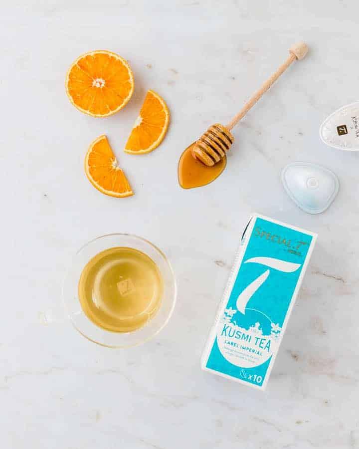 Glas mit Tee, orangen, und honig auf einem weissen hintergrund