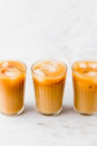 3 glasses of thai iced tea filled with iced cubes