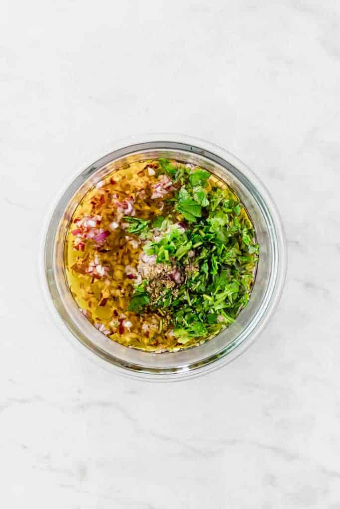 ingredients for chimichurri sauce in a glass bowl on a white table