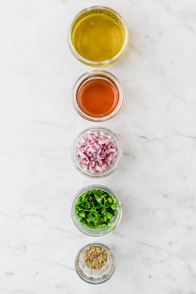 chimichurri ingredientes lined up on a white table