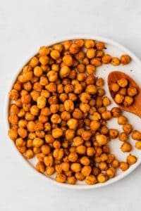 oven roasted chickpeas on a white plate with a wooden spoon