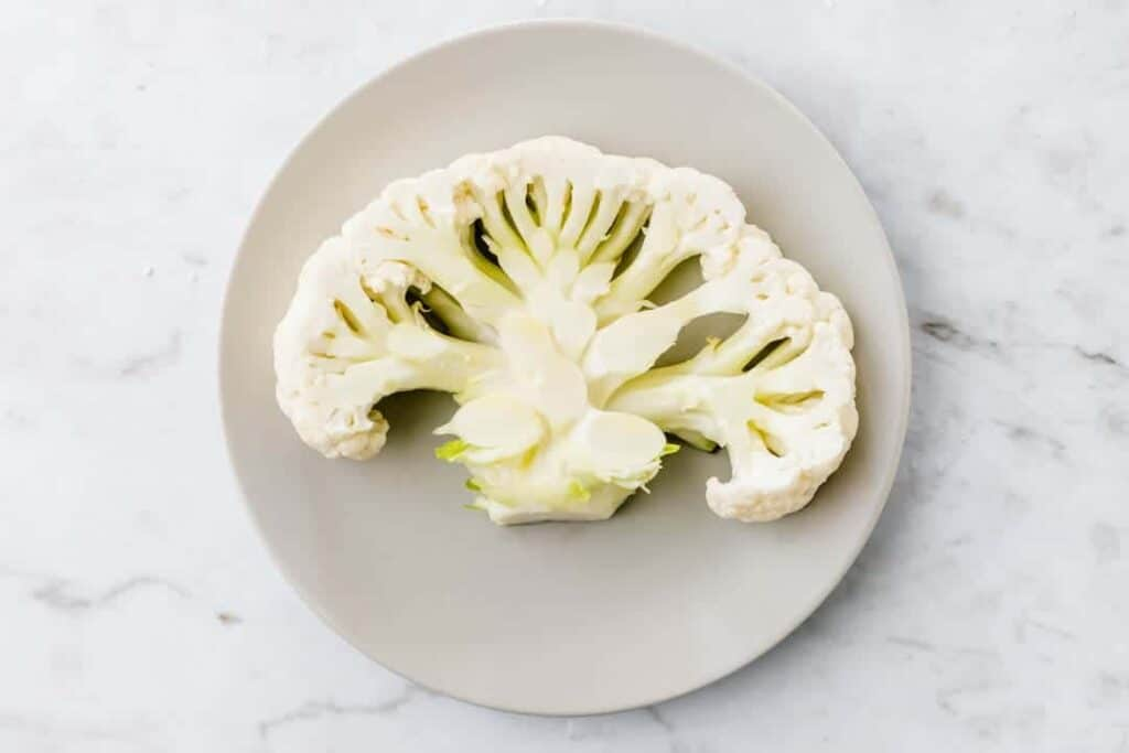 raw cauliflower steak on a grey plate