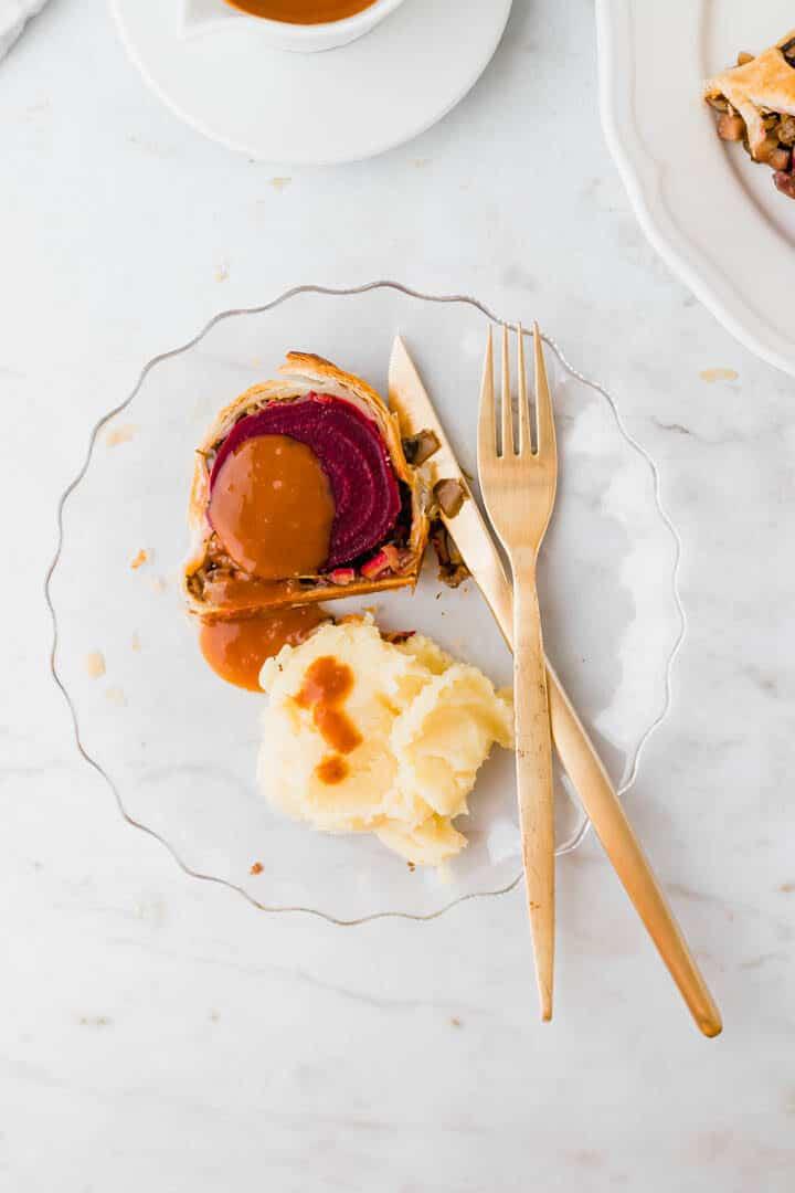 eine scheibe beet wellington serviert mit bratensauce und kartoffelbrei