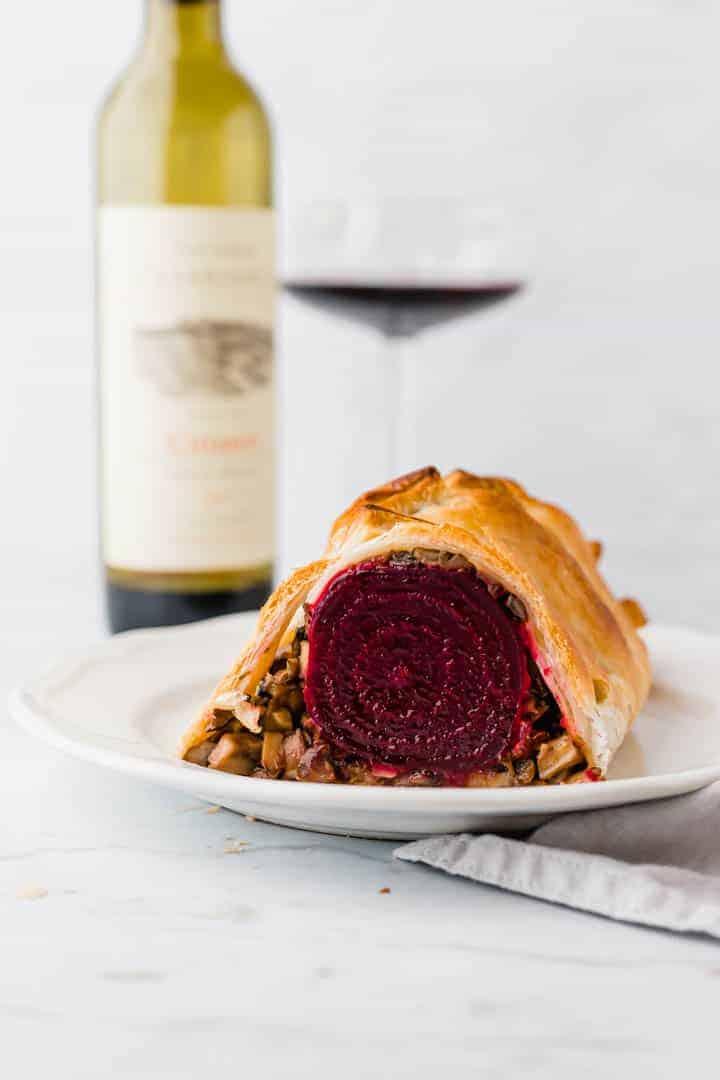 veganes beet wellington serviert mit einer flasche rotwein
