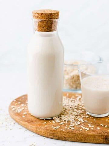 hafermilch in einer glasflasche neben einem glas