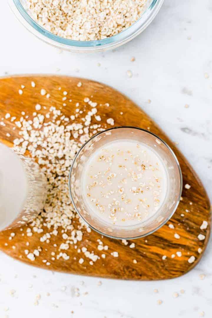 hafermilch in einem glas mit haferflocken obendrauf