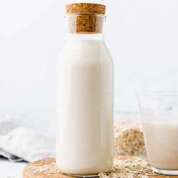 best oat milk served in a glass bottle on a wooden plate
