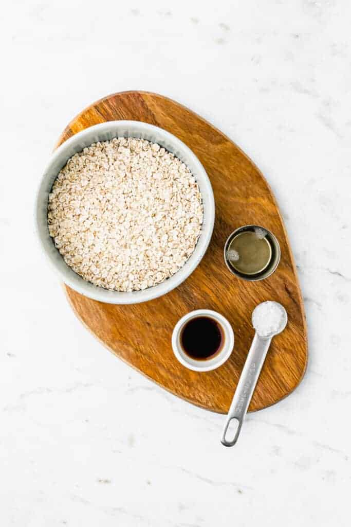 ingredients for oat milk recipe on a wooden plate