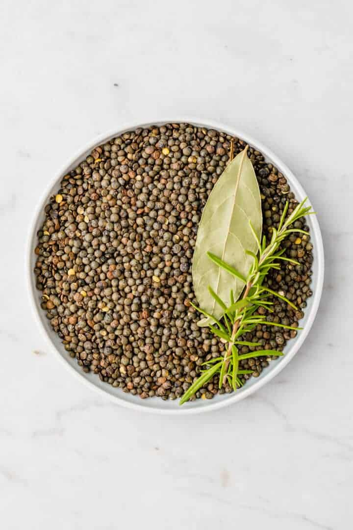 green puy lentils in a small blue bowl and fresh herbs