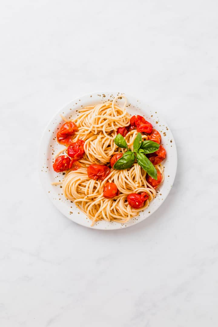 The tastiest and juiciest roasted cherry tomato pasta ever! This vegan pasta recipe with oven roasted cherry tomatoes is super easy, quick, and a perfect family dinner! #cherry #tomatoes #recipes #pasta #roasted #oven #sauce #vegan
