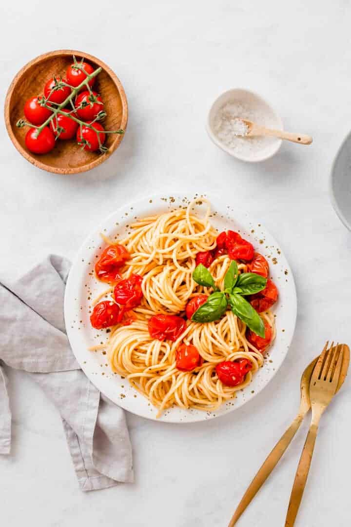 spaghetti with roasted cherry tomatoes and fresh basil on a white plate next to golden cutlery