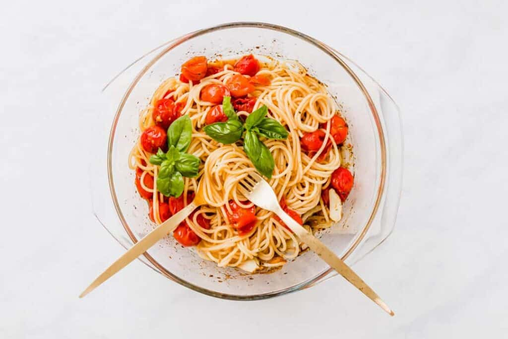 a baking dish full of cherry tomato pasta with golden cutlery