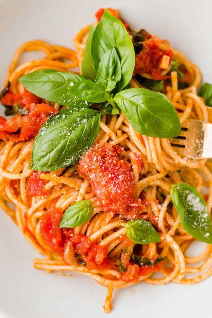 pasta al pomodoro serviert mit frischem basilikum und veganem parmesan