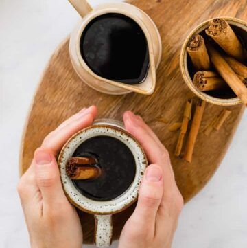 cafe de olla served in brown cups with cinnamon